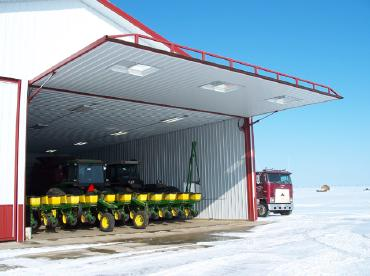 Outside view of a large garage with the door open showing farming tractors
