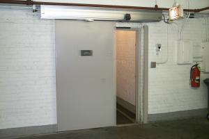 A large door on a track against a wall sliding open